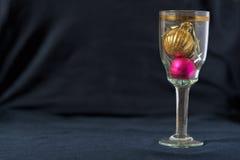 Σφαίρες παιχνιδιών Χριστουγέννων σε ένα ποτήρι της σαμπάνιας Μαύρη ανασκόπηση Στοκ Φωτογραφίες