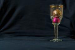 Σφαίρες παιχνιδιών Χριστουγέννων σε ένα ποτήρι της σαμπάνιας Μαύρο υπόβαθρο σύστασης Στοκ φωτογραφίες με δικαίωμα ελεύθερης χρήσης