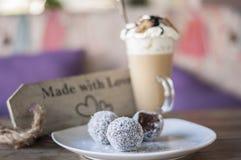 Σφαίρες σοκολάτας στο άσπρους πιάτο και τον καφέ latte με τη σοκολάτα καραμέλας στην κορυφή στοκ εικόνα
