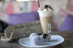 Σφαίρες σοκολάτας στο άσπρους πιάτο και τον καφέ latte με τη σοκολάτα καραμέλας στην κορυφή στοκ εικόνες