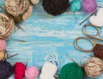 Σφαίρες του νήματος μαλλιού, του ψαλιδιού και των πλέκοντας βελόνων σε έναν ξύλινο πίνακα Στοκ Εικόνες