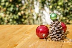 Σφαίρες Χριστουγέννων δίπλα στο pinecone στον ξύλινο πίνακα, με ένα πράσινο β Στοκ Φωτογραφία