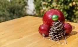 Σφαίρες Χριστουγέννων δίπλα στο pinecone στον ξύλινο πίνακα Στοκ φωτογραφία με δικαίωμα ελεύθερης χρήσης