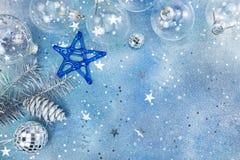 Σφαίρες Χριστουγέννων γυαλιού με τον κλάδο αστεριών και έλατου στο μπλε backgroun Στοκ Φωτογραφία