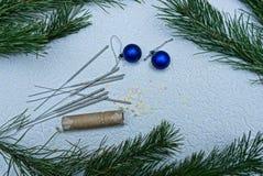 Σφαίρες Χριστουγέννων και φω'τα της Βεγγάλης με τις κροτίδες και τους πράσινους κλάδους Στοκ Φωτογραφία
