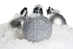 Σφαίρες Χριστουγέννων με το χιόνι στο άσπρο υπόβαθρο Στοκ Φωτογραφία