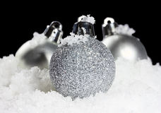 Σφαίρες Χριστουγέννων με το χιόνι στο μαύρο υπόβαθρο Στοκ φωτογραφία με δικαίωμα ελεύθερης χρήσης