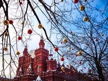 Σφαίρες Χριστουγέννων στους κλάδους δέντρων στο κόκκινο τετράγωνο Στοκ Φωτογραφία