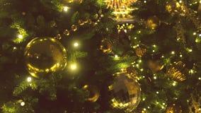 Σφαίρες Χριστουγέννων του χρυσού χρώματος και των γιρλαντών με τους βολβούς στους κλάδους του χριστουγεννιάτικου δέντρου, άποψη κ φιλμ μικρού μήκους