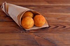 Σφαίρες Arancini Τηγανισμένες σφαίρες ρυζιού στο έγγραφο για το καφετί ξύλινο υπόβαθρο snack Στοκ Φωτογραφίες