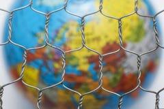 Σφαιρικός χάρτης πίσω από έναν φράκτη καλωδίων Στοκ Φωτογραφία