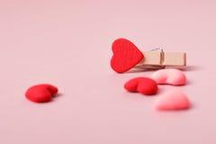 Σφιγκτήρας και μικρές καρδιές στο ανοικτό ροζ υπόβαθρο Στοκ Φωτογραφία
