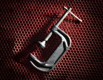 Σφιγκτήρας στο κόκκινο πλέγμα Στοκ Φωτογραφία