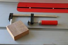Σφιγκτήρας Φ με την κόκκινη λαβή στο επιτραπέζιο πριόνι Στοκ Εικόνες