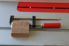 Σφιγκτήρας Φ με την κόκκινη λαβή στο επιτραπέζιο πριόνι Στοκ Εικόνα
