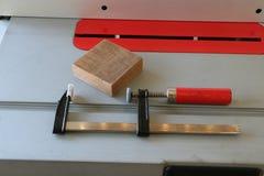 Σφιγκτήρας Φ με την κόκκινη λαβή στο επιτραπέζιο πριόνι Στοκ εικόνες με δικαίωμα ελεύθερης χρήσης