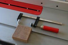 Σφιγκτήρας Φ με την κόκκινη λαβή στο επιτραπέζιο πριόνι Στοκ φωτογραφίες με δικαίωμα ελεύθερης χρήσης