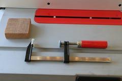Σφιγκτήρας Φ με την κόκκινη λαβή στο επιτραπέζιο πριόνι Στοκ φωτογραφία με δικαίωμα ελεύθερης χρήσης