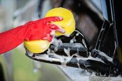 Σφουγγάρι εκμετάλλευσης χεριών που πλένει τους δευτερεύοντες καθρέφτες του αυτοκινήτου στοκ εικόνες
