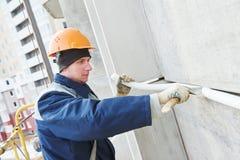 Σφραγίζοντας ένωση γυψαδόρων προσόψεων της οικοδόμησης του τοίχου με putty τη μαστίχα στοκ εικόνα