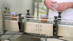 Σφραγίζοντας προϊόν χειριστών στη τελική φάση της γιαούρτι-πλήρωσης παραγωγής Το γιαούρτι ασφαλίστρου συμπλήρωσε τα φλυτζάνια αγγ απόθεμα βίντεο