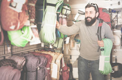 Σφριγηλός αρσενικός πελάτης που εξετάζει αναρριμένος στον εξοπλισμό στον αθλητισμό eq Στοκ φωτογραφία με δικαίωμα ελεύθερης χρήσης