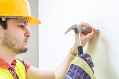 Σφυρί ένα καρφί στον τοίχο εργαζόμενος σφυριών Στοκ Εικόνες