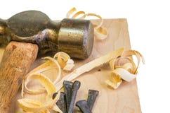 Σφυρί και καρφιά σε ένα ξύλινο χαρτόνι Στοκ Εικόνες