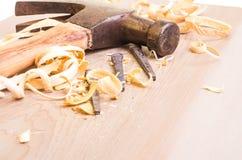 Σφυρί και καρφιά σε ένα ξύλινο χαρτόνι Στοκ εικόνες με δικαίωμα ελεύθερης χρήσης