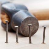 Σφυρί και καρφιά στην ξύλινη σανίδα Στοκ Φωτογραφίες