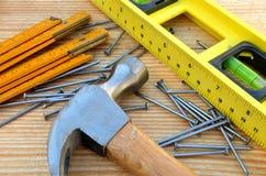 Σφυρί νυχιών, μετρητής ξυλουργών, water-level και καρφιά Στοκ Εικόνες