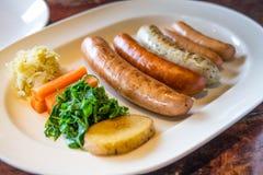Σχάρα λουκάνικων με το λαχανικό στο άσπρο πιάτο στοκ εικόνα