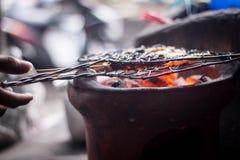 Σχάρα sate και tempe στα εικονικά παραδοσιακά τρόφιμα angkringan με τη φωτογραφία χεριών που λαμβάνεται στο yogyakarta Ινδονησία  Στοκ εικόνες με δικαίωμα ελεύθερης χρήσης