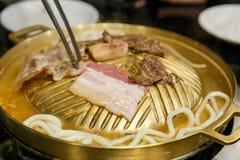 Σχάρα Udon και χοιρινού κρέατος BBQ στο τηγάνι ορείχαλκου Στοκ Εικόνες