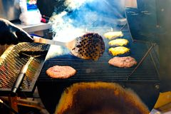 Σχάρες νεαρών άνδρων κάποιο είδος μαριναρισμένων κρέατος και λαχανικού στη σχάρα αερίου κατά τη διάρκεια του θερινού χρόνου στοκ φωτογραφίες