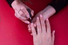 Σχέδιο ενός βερνικιού σε ένα μικρό δάχτυλο ήπια ρόδινη λάκκα Στοκ Εικόνα
