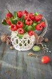 Σχέδιο ευχετήριων καρτών Πάσχας με τη δέσμη των κόκκινων τουλιπών στο αγροτικό β στοκ φωτογραφίες