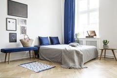 Σχέδιο κρεβατοκάμαρων στο σύγχρονο διαμέρισμα Κρεβάτι με τα σκούρο μπλε μαξιλάρια και το γκρίζο duvet και κάλυμμα δίπλα στο παράθ στοκ εικόνες