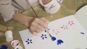 Σχέδιο μαθητριών με τη ευχετήρια κάρτα γκουας με τα λουλούδια για τη μητέρα της απόθεμα βίντεο