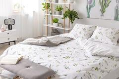 Σχέδιο πράσινων εγκαταστάσεων στην άσπρη κλινοστρωμνή και μαξιλάρια σε ένα κρεβάτι σε ένα εσωτερικό κρεβατοκάμαρων αγάπης φύσης στοκ φωτογραφία