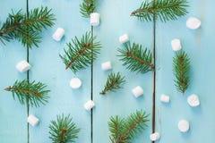 Σχέδιο Χριστουγέννων με τον κλάδο του δέντρου και marshmallows έλατου στο ξύλινο υπόβαθρο Στοκ φωτογραφία με δικαίωμα ελεύθερης χρήσης