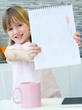 Σχέδιο παιδιών με τα κραγιόνια, συνεδρίαση στον πίνακα στην κουζίνα Στοκ Εικόνα