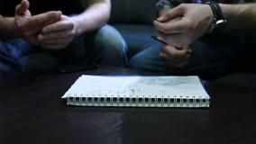 Σχέδιο σχεδίων Χέρια των νέων που επισύρουν την προσοχή ένα σχέδιο με τη μάνδρα στο σημειωματάριο στο γραφείο κατά τη διάρκεια τη φιλμ μικρού μήκους