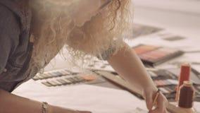Σχέδιο σχεδιαστών μόδας και χρώμα Το θηλυκό σύρει τα σκίτσα για τα ενδύματα στο ατελιέ απόθεμα βίντεο