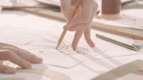 Σχέδιο σχεδιαστών μόδας σε ένα στούντιο Το χέρι γυναικών ` s επισύρει την προσοχή σε χαρτί Κινηματογράφηση σε πρώτο πλάνο φιλμ μικρού μήκους