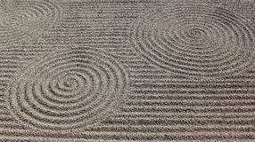Σχέδιο της Zen στο μαζεμένο με τη τσουγκράνα αμμοχάλικο στοκ φωτογραφία