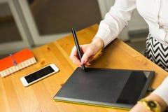 Σχέδιο χεριών γυναικών με την ταμπλέτα γραφικής παράστασης, εργαζόμενος σχεδιαστής στοκ φωτογραφίες