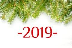 Σχήματα 2019 για ένα άσπρο υπόβαθρο, πλαίσιο των κλάδων έλατου στοκ φωτογραφία με δικαίωμα ελεύθερης χρήσης