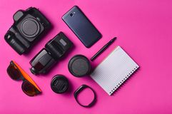 Σχεδιάγραμμα συσκευών και εξαρτημάτων σε ένα ρόδινο υπόβαθρο Φωτογραφικός εξοπλισμός, πορτοφόλι με τα δολάρια, έξυπνο ρολόι, smar στοκ εικόνες