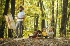 Σχεδιασμός από τη ζωή Καλλιτέχνης ζωγράφων με την οικογενειακή χαλάρωση στη δασική ζωγραφική στη φύση Νέα εικόνα έναρξης Συλλάβετ στοκ φωτογραφία
